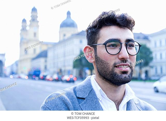 Germany, Munich, portrait of smiling young businessman in the city