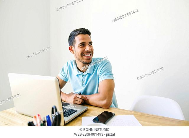 Young man working in office, using laptop