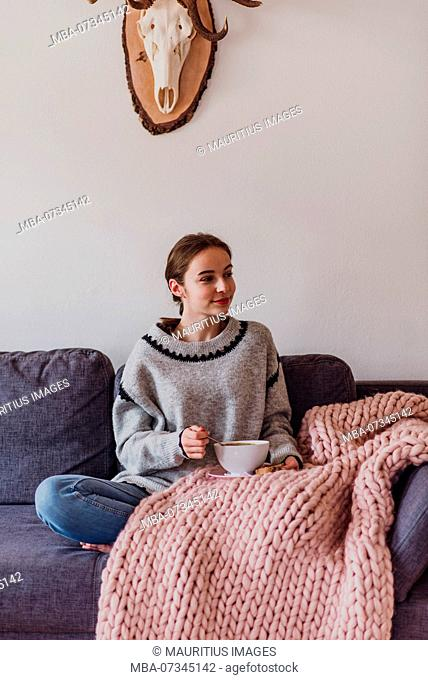 young woman sitting on sofa and eating a soup