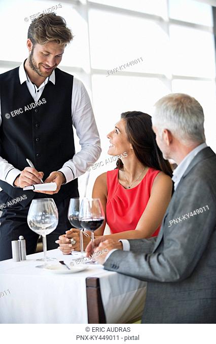 Waiter taking orders from a couple in a restaurant