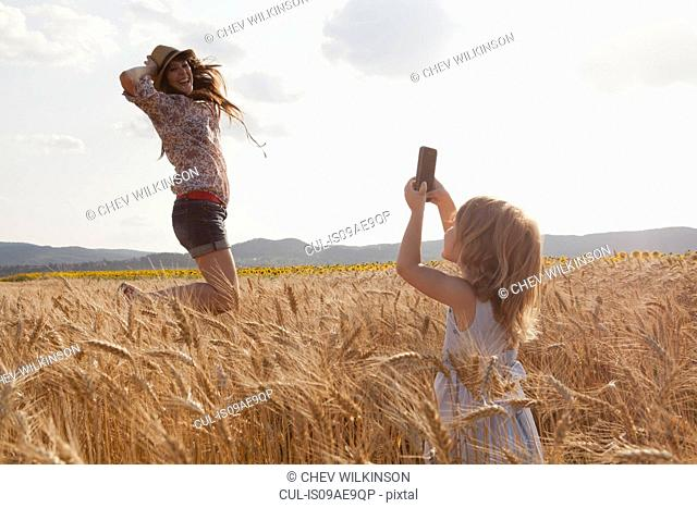 Girl taking photograph of mother in wheat field jumping