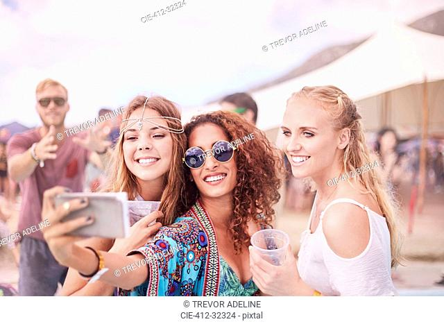 Young women posing for selfie at music festival