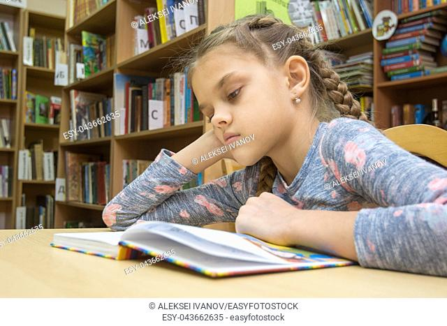 A girl of ten years old is reading a book in the reading room