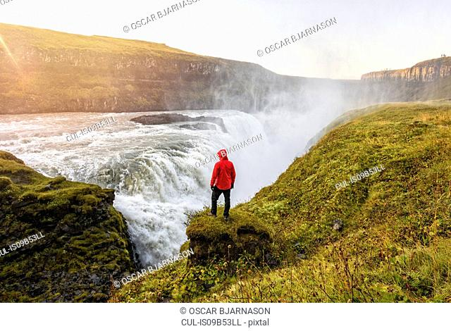 Hiker watching waterfall, Gullfoss, Iceland