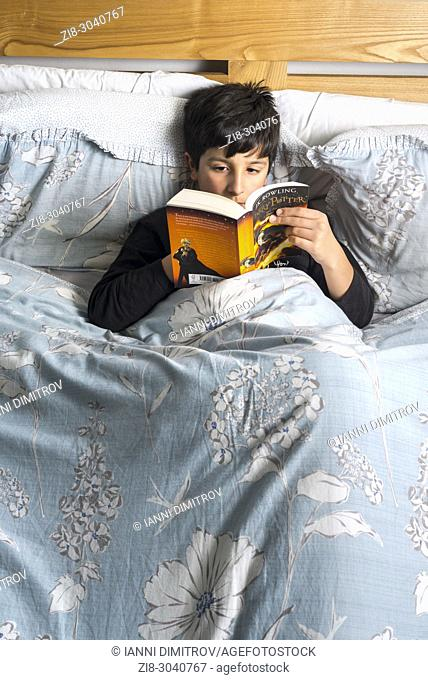 Boy reading book in bed , Harry Potter by J. K. Rowling , UK