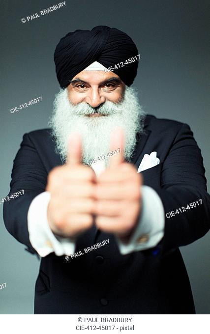 Portrait enthusiastic well-dressed senior man wearing turban, gesturing thumbs-up