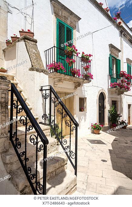 A colourful Baroque side street of Locorotondo, in the Itria Valley, Puglia, Italy