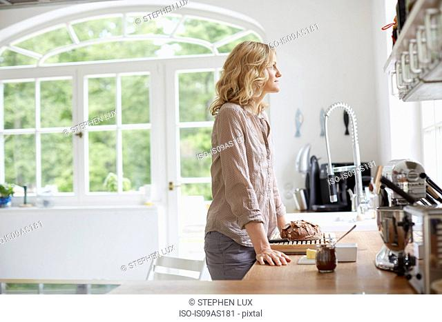 Mid adult woman standing at kitchen counter, looking out of window