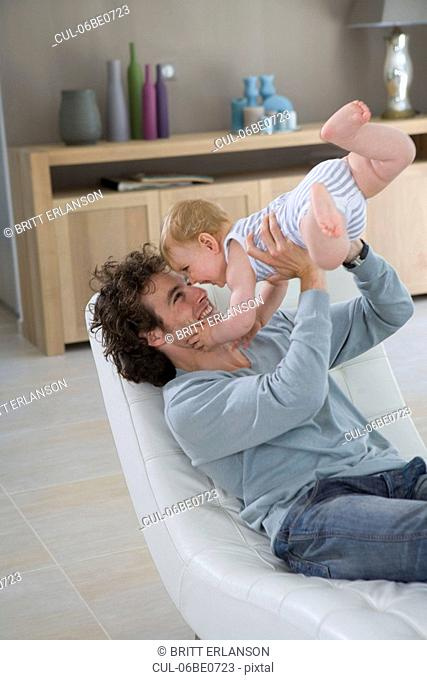 Father holds up baby in chair home