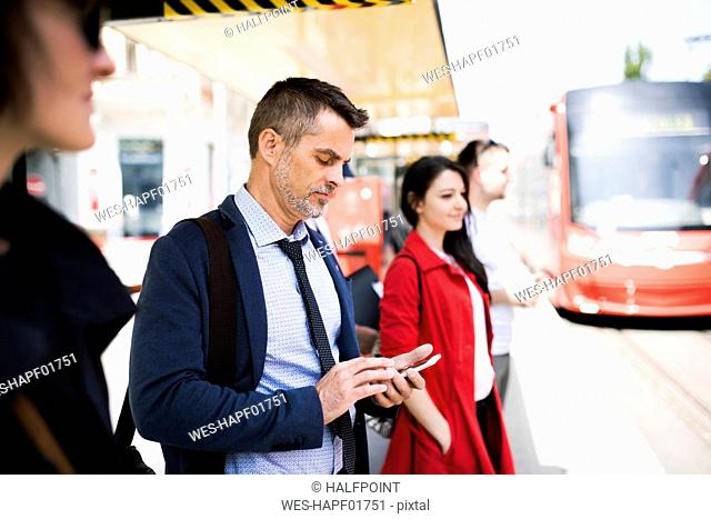 Businessman with smartphone waiting at the bus stop