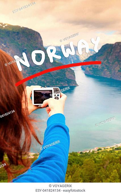 Tourism vacation and travel. Woman tourist taking photo with camera, enjoying Aurland fjord view from Stegastein viewpoint, Norway Scandinavia