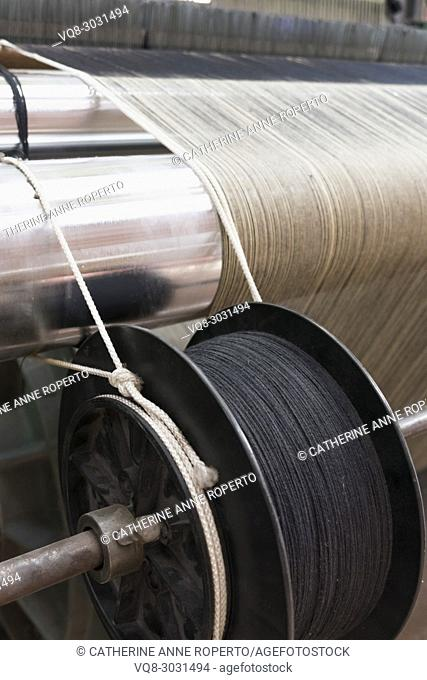 Jacquard fabric loom with neutral and grey thread on reflective steel cylindars and dark metal industrial spool, La Manufacture de Roubaix, France