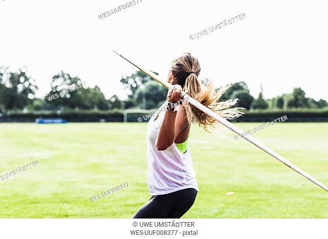 Young woman throwing javelin