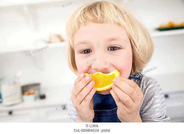 Portrait of cute girl in kitchen holding orange slice to her mouth