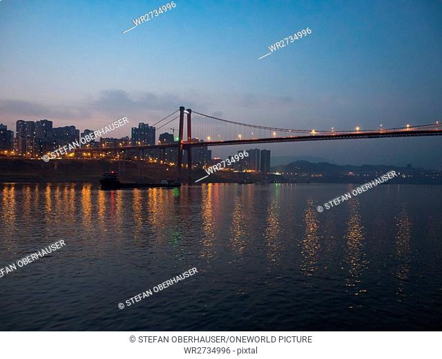 China, Chongqing, river cruise on the Yangtze River, Illuminated city and bridge over the Yangtze River at Zhongxian
