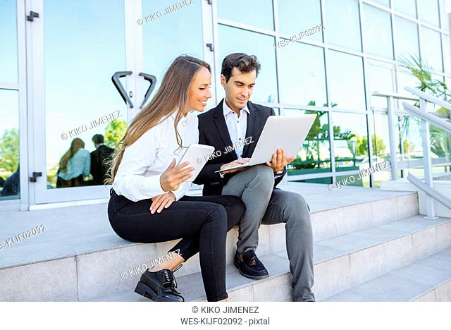 Businesswoman and businessman working with tablet and laptop outside office building