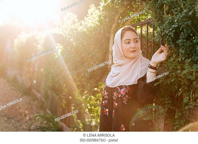 Young woman wearing hijab admiring plants