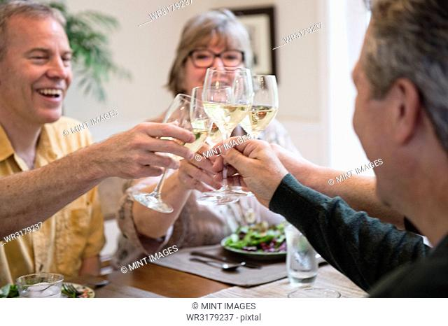 Senior couples toasting a home dinner party with glasses of white wine