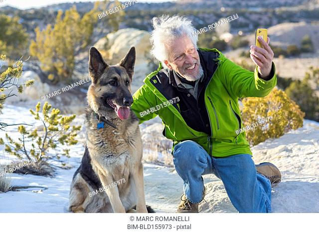Older man taking cell phone photograph with dog on rock formations
