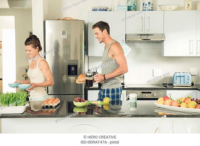 Young couple carrying breakfast from kitchen counter