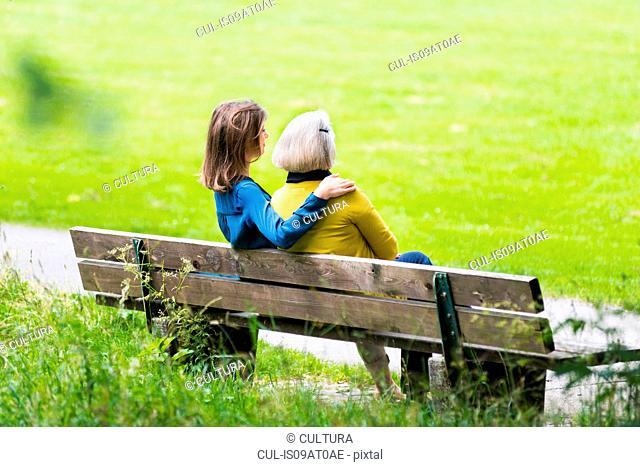 Rear view of senior woman and daughter relaxing on park bench