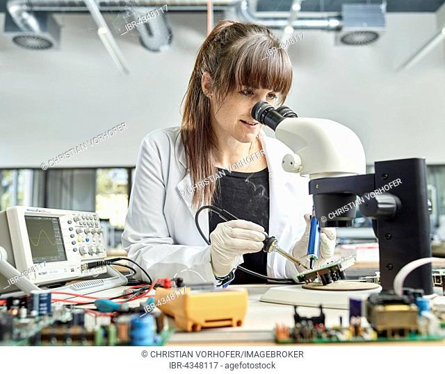 Female technician, 20-25 years, with a white lab coat, soldering a circuit board in an electronics laboratory, Wattens, Innsbruck Land, Tyrol, Austria