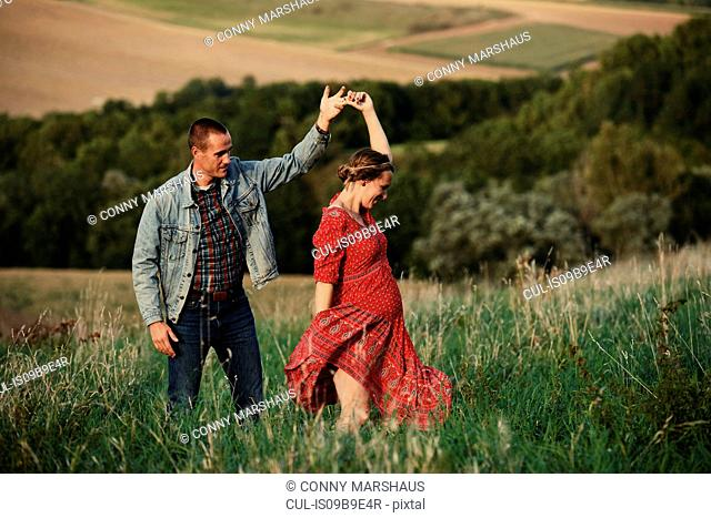 Romantic pregnant mid adult couple dancing in field