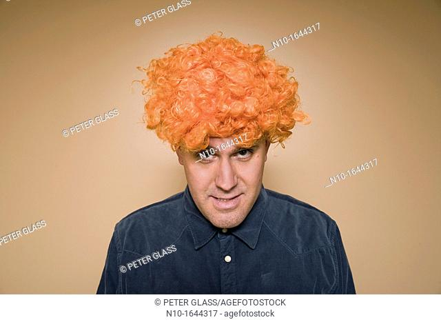Middle-age man wearing an orange wig
