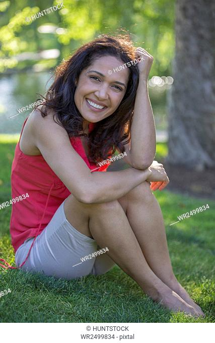 Portrait of happy Hispanic woman sitting in a park