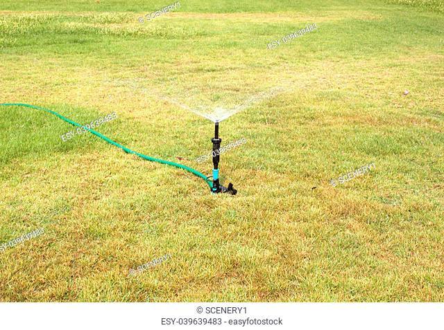 Water sprinkler. Irrigation system - technique of watering in the garden. Lawn sprinkler spraying water over green grass