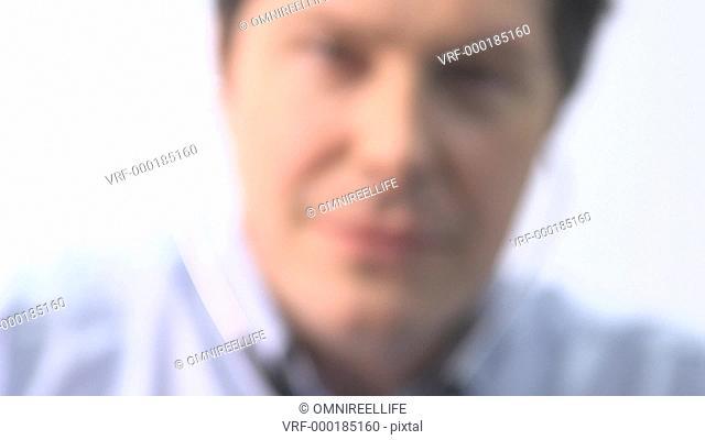 Male doctor holding stethoscope near lens