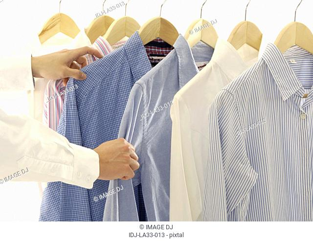 Cropped view of a person selecting the shirts