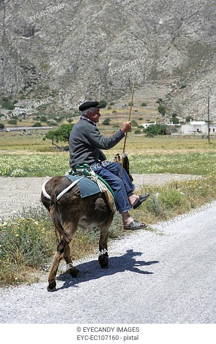 A senior man riding a donkey