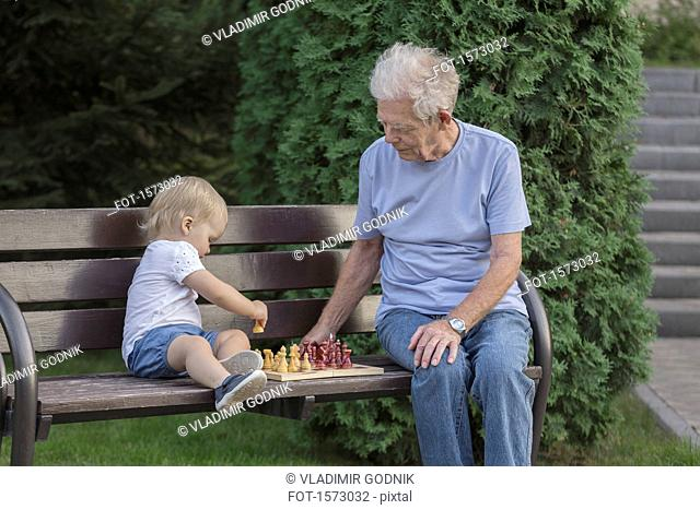 Senior man playing chess with granddaughter on park bench against tree
