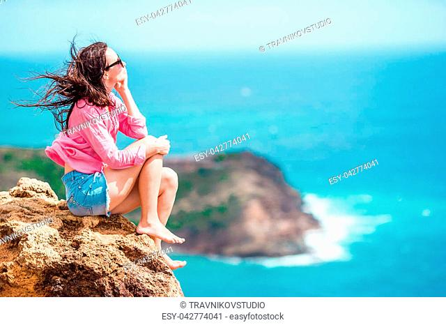 Young woman enjoying breathtaking views from Shirley Heights on Antigua island