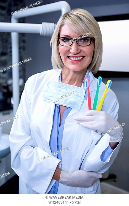Portrait of smiling dentist holding three toothbrushes
