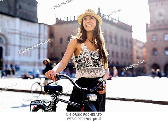 Italy, Bologna, portrait of fashionable young woman pushing bicycle in the city