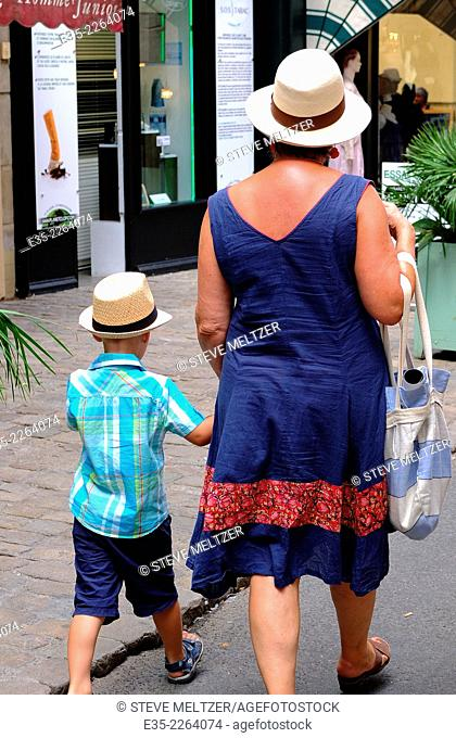 A grandmother and her grandson walk together on a street wearing straw hats