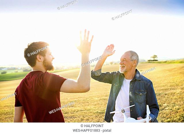 Senior father and his adult son with drone on a field