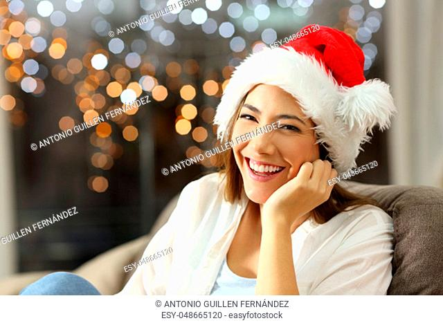 Happy woman looking at you on chritmas sitting on a couch in the living room at home