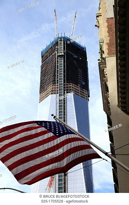 One World Trade Center formerly known as the Freedom Tower under construction in the new World Trade Center complex with a US flag in foreground  Lower...