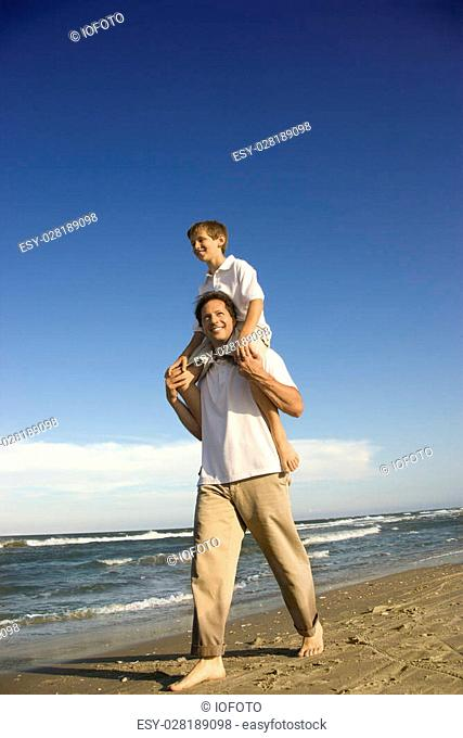 Caucasian father with pre-teen boy on shoulders on beach
