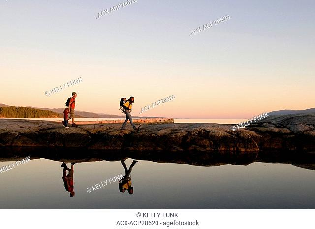 A young family hikes the Pacific ocean shoreline in late afternoon light, near Powell River, on the Sunshine coast of the Vancouver coast and mountain region of...