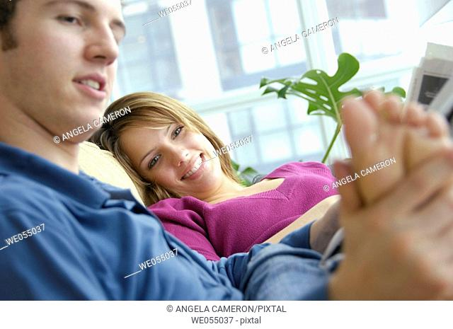 young couple together at home on the sofa