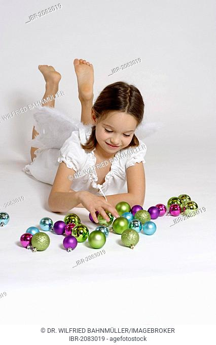 Girl dressed up as Christmas angel, Christ Child with Christmas baubles