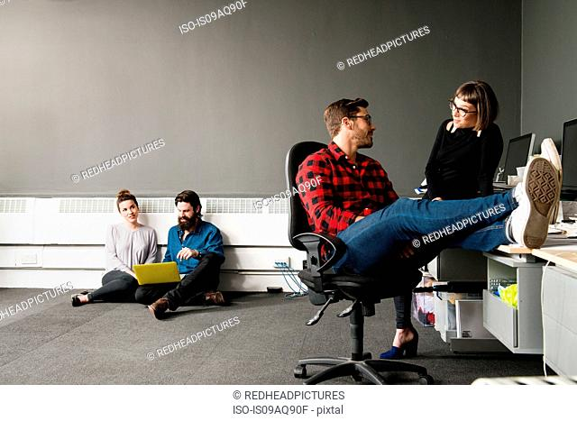 Young man sitting on office chair with feet up on desk