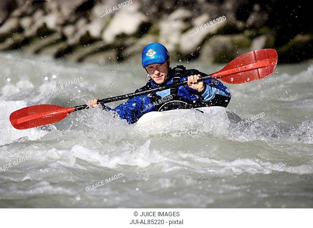Person paddling kayak in whitewater