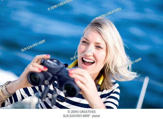 Woman using binoculars on boat