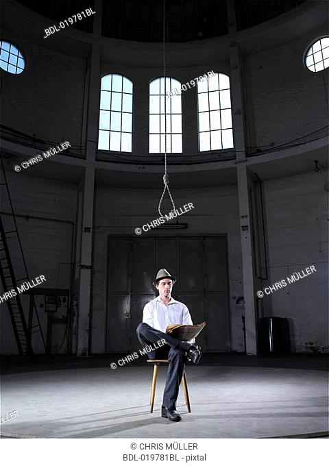 man sitting in empty building under rope reading newspaper