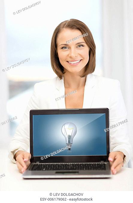 education, business, technology and internet concept - smiling woman with laptop computer in office